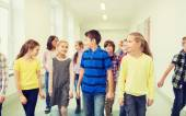 Group of smiling school kids walking in corridor — Stock Photo