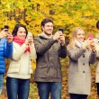 Smiling friends with smartphones in city park — Stock Photo #81159654
