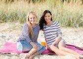 Gelukkig tiener meisjes of jonge vrouwen op strand — Stockfoto