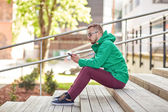 Young hipster man with smartphone in city — Stock Photo