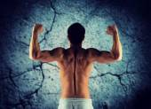 Jonge man tonen biceps en spieren — Stockfoto