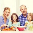 Happy family with two kids making dinner at home — Stock Photo #81600872
