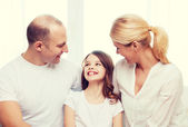 Smiling parents and little girl at home — Stock Photo