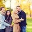 Group of smiling men and women in autumn park — Stock Photo #81692232