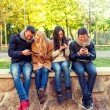 Smiling friends with smartphones in city park — Stock Photo #81692278