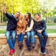 Smiling friends with smartphones in city park — Stock Photo #81692284