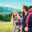 Smiling couple with backpacks hiking — Stock Photo #81692940