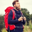 Man with backpack and binocular outdoors — Stock Photo #81692998