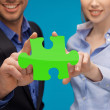 Man and woman hands with green puzzle — Stock Photo #81693106