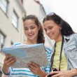 Smiling teenage girls with map and camera outdoors — Stock Photo #81694082