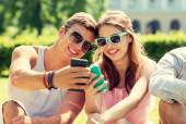 Smiling friends with smartphones sitting in park — Stock Photo