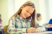 Smiling school girl writing test in classroom — Stock Photo