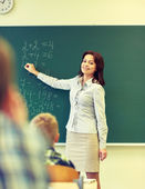 School kids and teacher writing on chalkboard — Stock Photo