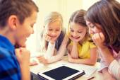 Group of school kids with tablet pc in classroom — Stock Photo