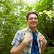 Smiling young man with backpack hiking in woods — Stock Photo #81800568