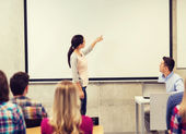 Group of students and smiling teacher in classroom — Stock Photo