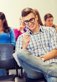 Group of smiling students with notebook — Stock Photo