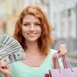 Happy woman with shopping bags and money on street — Stock fotografie #81910076