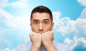 Scared man over blue sky and clouds background — Stock Photo
