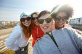 Group of happy friends taking selfie on street — Stock Photo