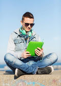 Happy young man with tablet pc and headphones — Stock Photo