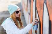 Teenage girl drawing graffiti with spray paint — Stock Photo