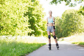 Happy young woman in rollerblades riding outdoors — Stock Photo