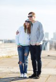 Happy teenage couple walking in city — Stock Photo