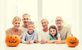 Happy family sitting with pumpkins at home — Stock Photo