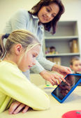 Little girl with teacher and tablet pc at school — Stock Photo