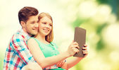 Couple with tablet pc taking selfie over green — Stock Photo