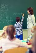 Teacher and schoolboy writing on chalk board — Stock Photo
