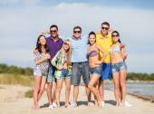 Group of happy friends hugging on beach — Stock Photo