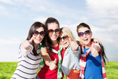 Happy teenage girls showing thumbs up at summer — Fotografia Stock