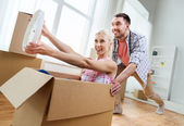 Couple with cardboard boxes having fun at new home — Stock Photo