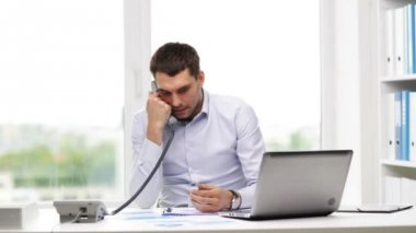 Angry businessman with laptop calling on phone — Stock Video