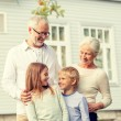 Happy family in front of house outdoors — Stock Photo #82262672