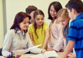 Group of school kids with teacher in classroom — Stock Photo