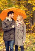 Smiling couple with umbrella in autumn park — Stock Photo