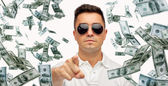 Man pointing on you with falling dollar money — Stock Photo