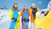Happy friends with snowboards and smartphone — Stock Photo
