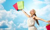 Smiling woman with shopping bag rising hands — Stock Photo