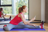 Smiling woman with smartphone stretching in gym — Stock Photo