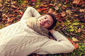 Close up of smiling young man lying in autumn park — Stock Photo