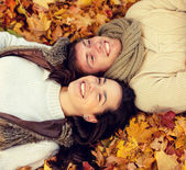Close up of smiling couple lying in autumn park — Stock Photo