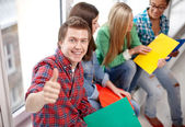 Group of happy students showing thumbs up — Stock Photo