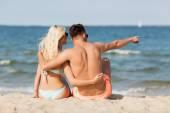 Happy couple in swimwear sitting on summer beach — Stock Photo