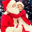 Smiling little girl with santa claus and gifts — Stock Photo #85002708