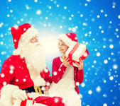 Smiling little girl with santa claus and gifts — Stock Photo