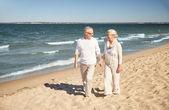 夏のビーチを歩いて幸せな先輩カップル — ストック写真